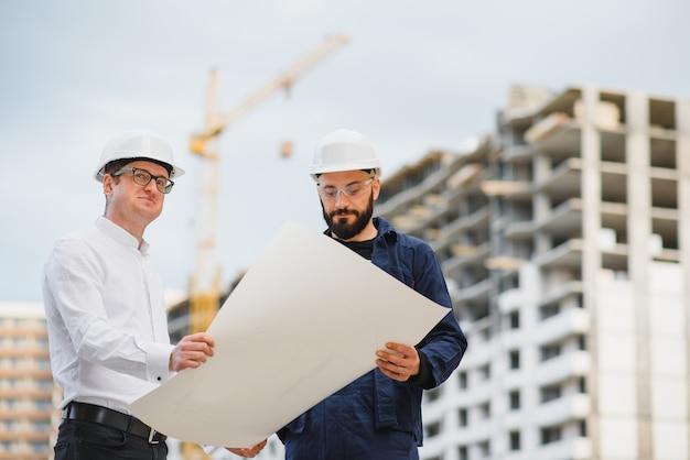 Widok inżyniera i pracownika sprawdzającego plan na budowie