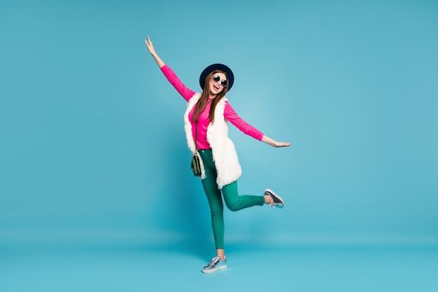 Widok jej ciała na całej długości ona ładna atrakcyjna urocza funky pozytywna wesoła wesoła dziewczyna tańczy, bawiąc się wygłupami odizolowana na jasnym, żywym połysku, wibrującym zielonym niebieskim turkusowym kolorze ściany