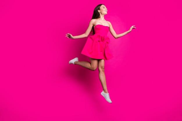 Widok jej ciała na całej długości ona ładna atrakcyjna wspaniała fascynująca beztroska wesoła długowłosa dziewczyna latająca, bawiąca się na białym tle na jasnym, żywym połysku, wibrującym różowym kolorze fuksji