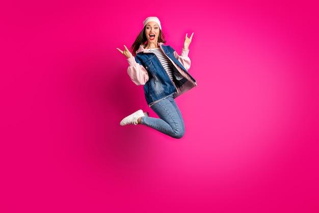 Widok jej pełnej długości ciała jest ładną atrakcyjną wesołą radosną ekstatyczną dziewczyną skaczącą, bawiąc się, pokazując znaki rogów odizolowane na jasnym, żywym połysku, wibrującym różowym kolorze fuksji