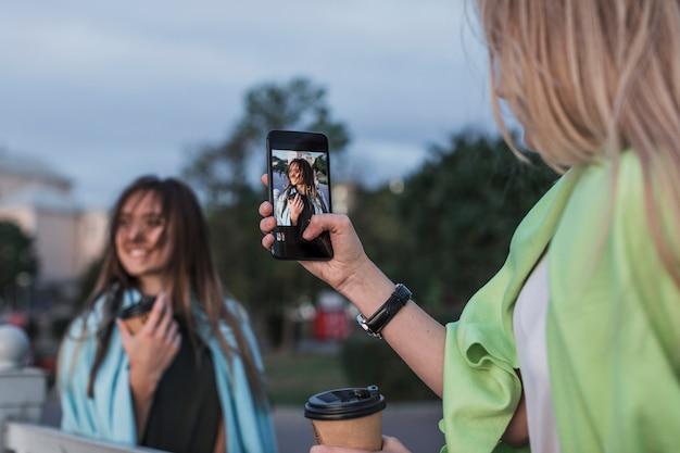 Widok kamery fotografującej młodą kobietę z tyłu