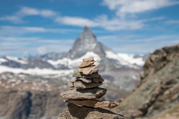 Widok kamieni równowagi, daleko matterhorn mountain, scena w parku narodowym zermatt, szwajcaria, europa. letni krajobraz, słoneczna pogoda, dramatyczne błękitne niebo i słoneczny dzień