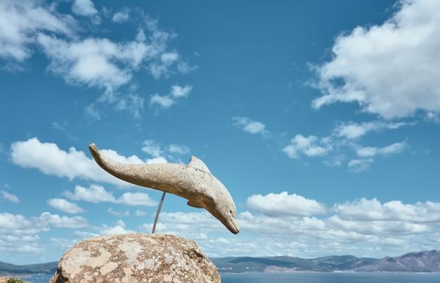 Widok kamiennego delfina nad morzem z chmurami i niebem w tle