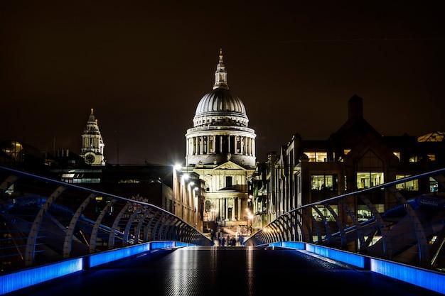 Widok katedry św. pawła z błękitnych świateł na moście millenium bridge w nocy w londynie