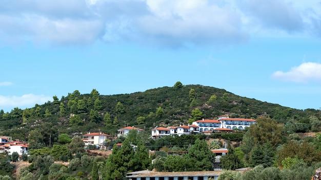 Widok kilku budynków wykonanych w identycznym stylu na wzgórzu porośniętym bujną zielenią w ouranoupolis w grecji