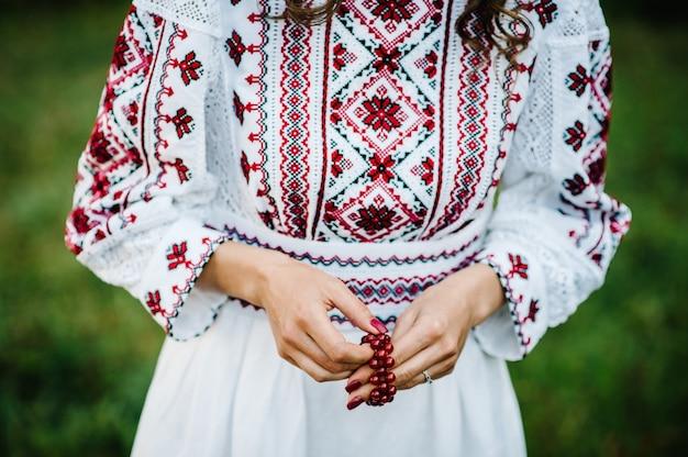 Widok kobiecej dłoni z czerwonym lakierem na paznokciach i bransoletką z kamieni szlachetnych w stylu rustykalnym.