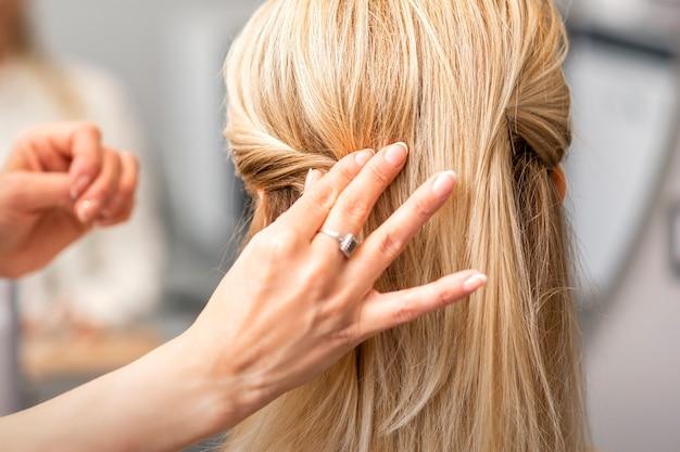 Widok kobiecej ręki fryzjera z tyłu modeluje fryzurę młodej kobiety blondynka w salonie fryzjerskim