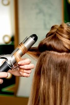 Widok kobiecych fryzjerów ręce kręcenie kobiet z lokówką w salonie fryzjerskim z tyłu