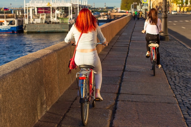 Widok kobiet jadących na rowerach po południu wzdłuż nasypu z tyłu