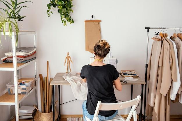 Widok kobieta krawiec pracujący w studio z tyłu