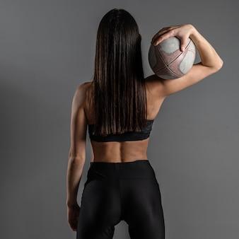 Widok kobiety gracz rugby z tyłu pozowanie trzymając piłkę