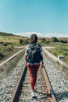Widok kobiety idącej wzdłuż linii kolejowych z nieba z tyłu.
