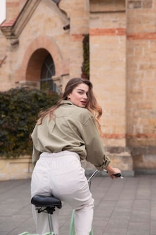 Widok kobiety jazdy na rowerze w mieście z tyłu
