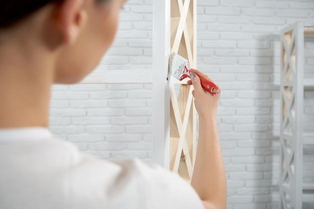 Widok kobiety malującej z drewnianym stojakiem z tyłu