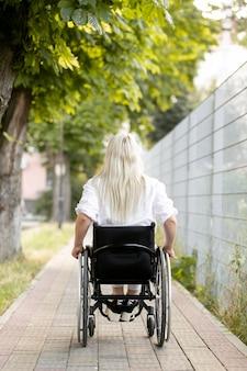 Widok kobiety na wózku inwalidzkim w mieście z tyłu