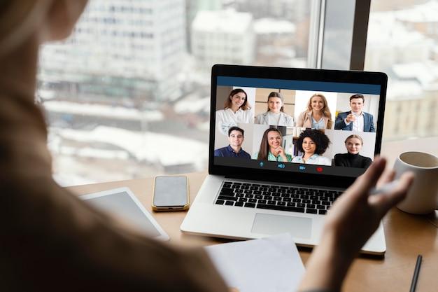 Widok kobiety o rozmowie wideo w pracy z tyłu
