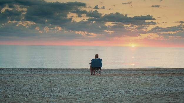 Widok kobiety podziwiającej zachód słońca nad morzem z tyłu w składanym fotelu turystycznym
