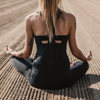 Widok kobiety robi joga na plaży z tyłu