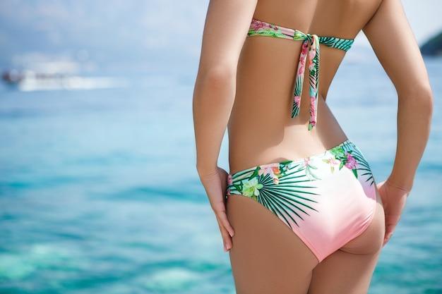Widok kobiety w bikini kwiatowy na plaży z tyłu