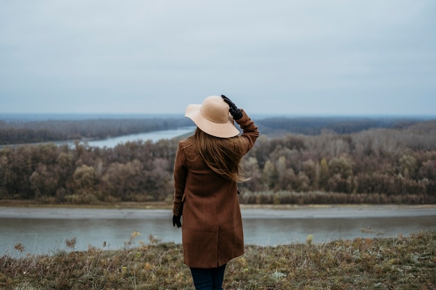 Widok kobiety w kapeluszu z tyłu, podziwiając widok na jezioro