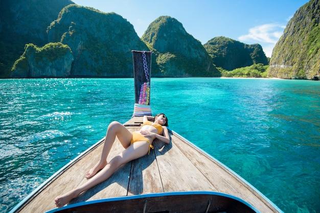 Widok kobiety w strój kąpielowy korzystających na tradycyjnej łodzi tajskiej longtail nad pięknymi górami i oceanem, wyspy phi phi, tajlandia