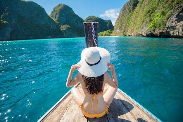 Widok kobiety w stroju kąpielowym, ciesząc się na tajskiej tradycyjnej łodzi longtail nad piękne góry i ocean, wyspy phi phi, tajlandia