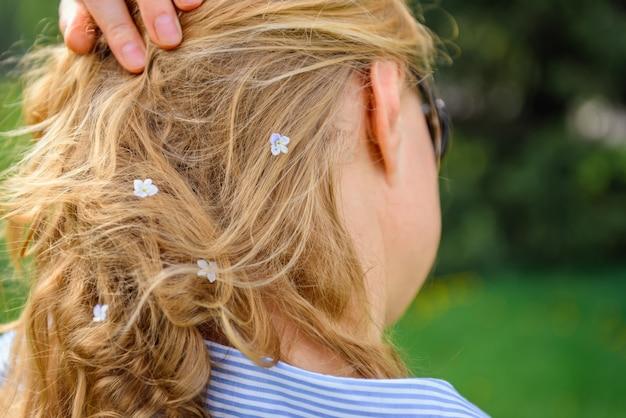 Widok kobiety włosy z małymi białymi kwiatami z tyłu. blondynka dotyka jej loków, zbliżenie. naturalne produkty do pielęgnacji włosów, wzmacniające wywar z korzeni włosów z ziół.