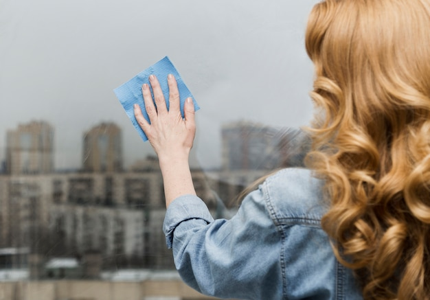 Widok kobiety wyciera okno z tyłu