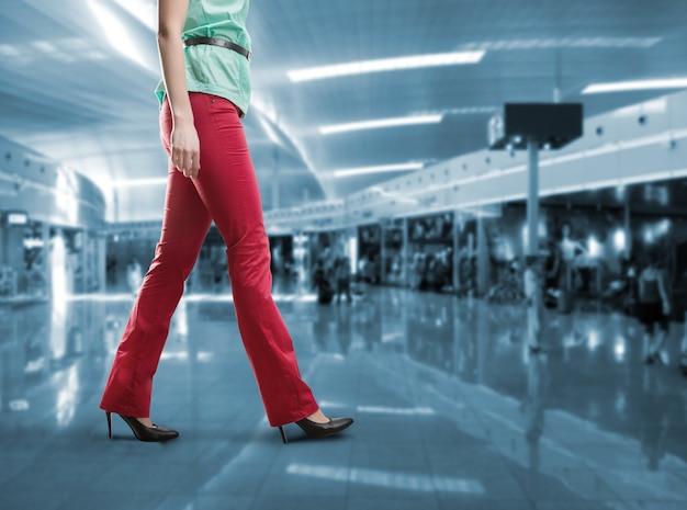 Widok kobiety z pasa idącej w czerwonych spodniach