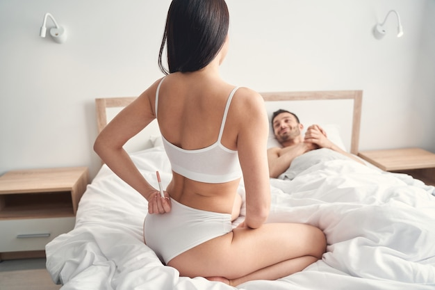 Widok kobiety z tyłu ukrywającej test ciążowy przed mężem za plecami