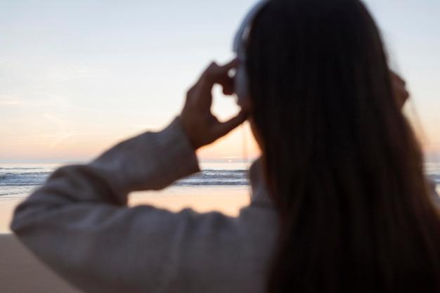Widok kobiety ze słuchawkami przy plaży z tyłu