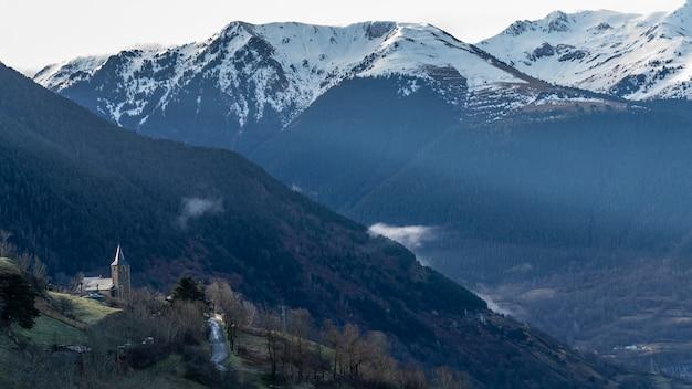 Widok kościoła miasta mont w vielha z zaśnieżonymi górami w tle.