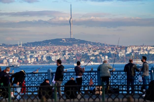 Widok krajobrazu na wieżę radiową kucuk camlica tv i rybaków na moście galata