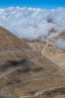 Widok krętej drogi i majestatycznych gór skalistych w indyjskich himalajach, region ladakh, indie. koncepcja przyrody i podróży