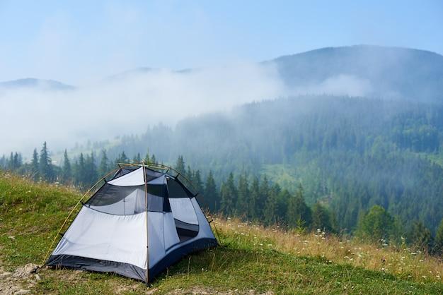 Widok latem mały wygodny nowoczesny biały i niebieski namiot turystyczny na trawiastym wzgórzu