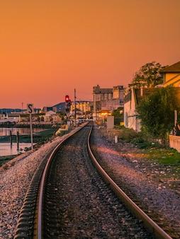 Widok linii kolejowej faros o zachodzie słońca.
