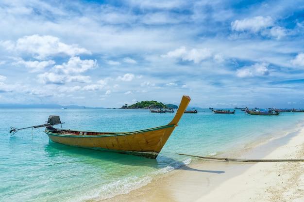 Widok łódź na tropikalnej plaży przy lipe thailand wyspą z białym piaskiem, turkusową ocean wodą i niebieskim niebem
