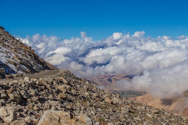 Widok majestatycznych gór skalistych na tle błękitnego nieba i białych chmur w indyjskich himalajach, region ladakh, indie. koncepcja przyrody i podróży