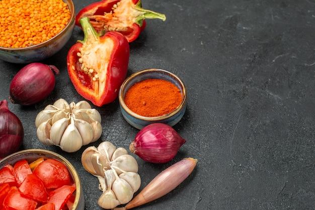 Widok makro po stronie warzyw miska pomidorów soczewicy przyprawy papryka na czarnym tle