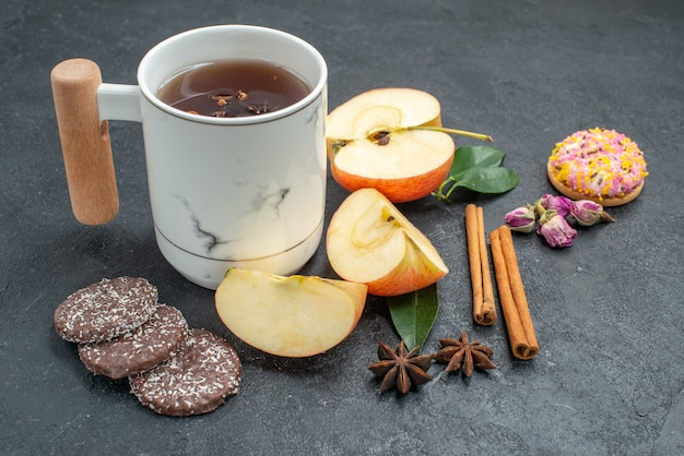 Widok makro z boku filiżanka herbaty ciasteczka filiżanka herbaty ziołowej jabłka plasterki laski cynamonu