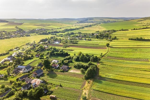 Widok małej wioski z lotu ptaka wygrywa wiosną wiele domów i zielonych pól uprawnych ze świeżą roślinnością po sezonie siewu w ciepły, słoneczny dzień.