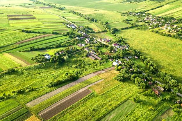 Widok małej wioski z lotu ptaka wygrywa wiosną wiele domów i zielonych pól uprawnych