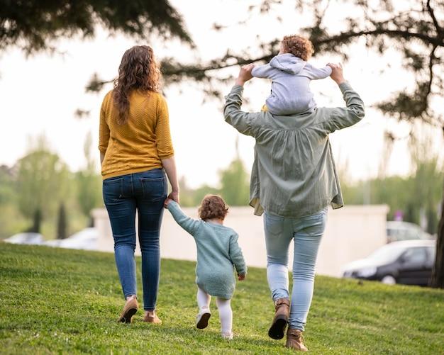 Widok matek lgbt na zewnątrz w parku z dziećmi z tyłu
