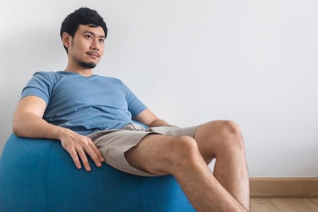 Widok męskich nóg na białym łóżku z telewizorem i rośliną