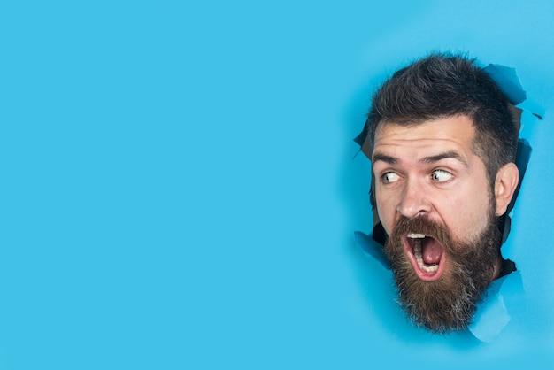 Widok męskiej twarzy przez dziurę w niebieskim papierze zaskoczony brodaty mężczyzna robiący dziurę w papierze ładny