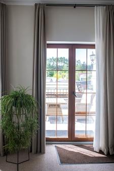 Widok metalowego kwietnika stojącego przy zamkniętych zewnętrznych dwuskrzydłowych szklanych drzwiach wychodzących na oświetloną słońcem werandę