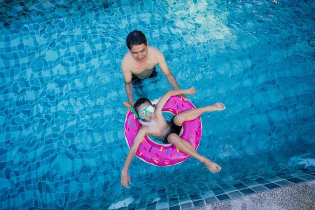 Widok mężczyzny i chłopca z pierścieniem pływać pływających w basenie.
