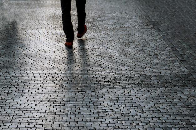 Widok miasta na chodnik z tyłu, mężczyzna spacerujący po chodniku w dobrze oświetlonym miejscu. ciemne cienie na bruku ulicy.