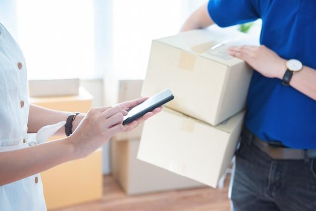 Widok młoda azjatykcia kobieta dołącza podpis w cyfrowym mądrze telefonie komórkowym po otrzymywać pakuneczek od kuriera doręczeniowego mężczyzna w domu ai technologii transportu pojęcie.