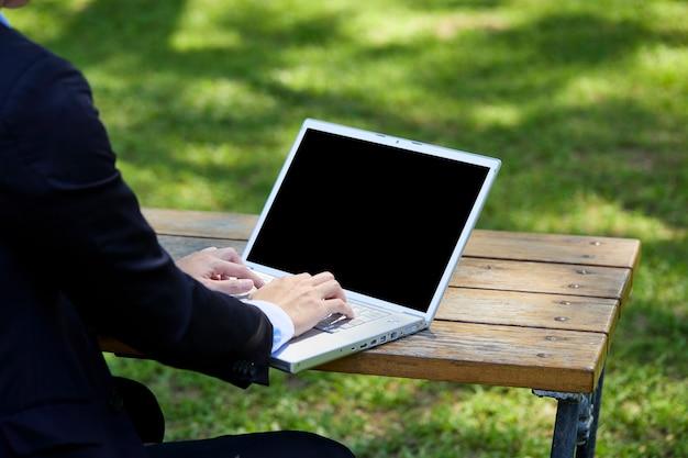 Widok młodego biznesmena siedzącego w ogrodzie do pracy z tyłu